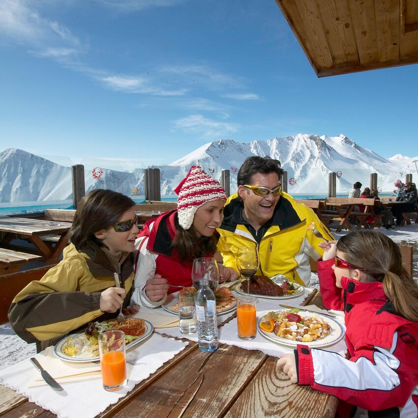 family skiing holiday tyrol eating traditional hut skiing area